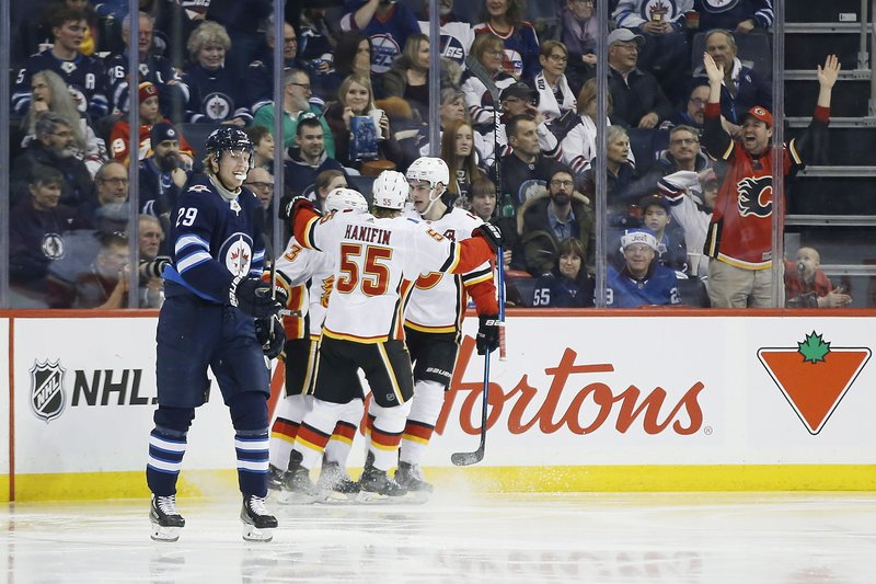Calgary Flames' Noah Hanifin (55), Johnny Gaudreau (13) and Sean Monahan (23) celebrate Gaudreau's goal that went off the stick of Winnipeg Jets right wing Patrik Laine (29) during second-period NHL hockey game action in Winnipeg, Manitoba, Thursday, Dec. (John Woods/The Canadian Press via AP)