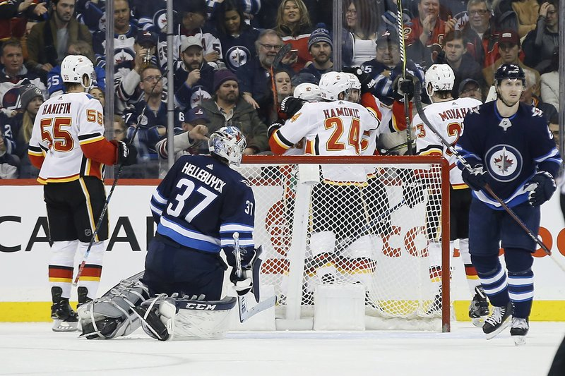 Calgary Flames celebrate Johnny Gaudreau's (13) second goal against Winnipeg Jets goaltender Connor Hellebuyck (37) during second-period NHL hockey game action in Winnipeg, Manitoba, Thursday, Dec. (John Woods/The Canadian Press via AP)