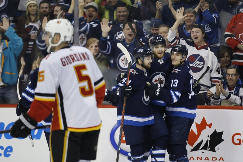 Winnipeg Jets' Josh Morrissey (44), Adam Lowry (17) and Brandon Tanev (13) celebrate Lowry's goal against the Calgary Flames during second-period NHL hockey game action in Winnipeg, Manitoba, Thursday, Dec. (John Woods/The Canadian Press via AP)