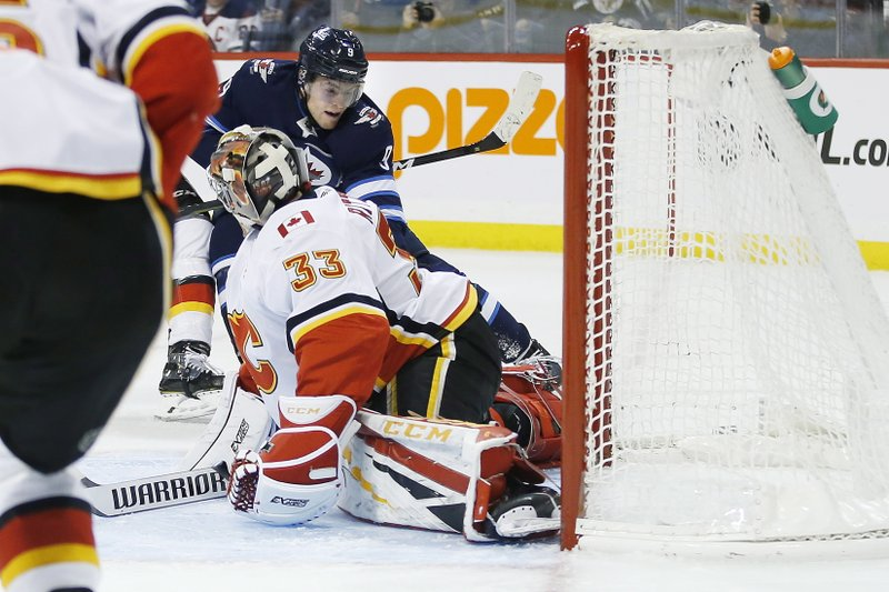 Winnipeg Jets' Andrew Copp's (9) shot is saved by Calgary Flames goaltender David Rittich (33) during second-period NHL hockey game action in Winnipeg, Manitoba, Thursday, Dec. (John Woods/The Canadian Press via AP)