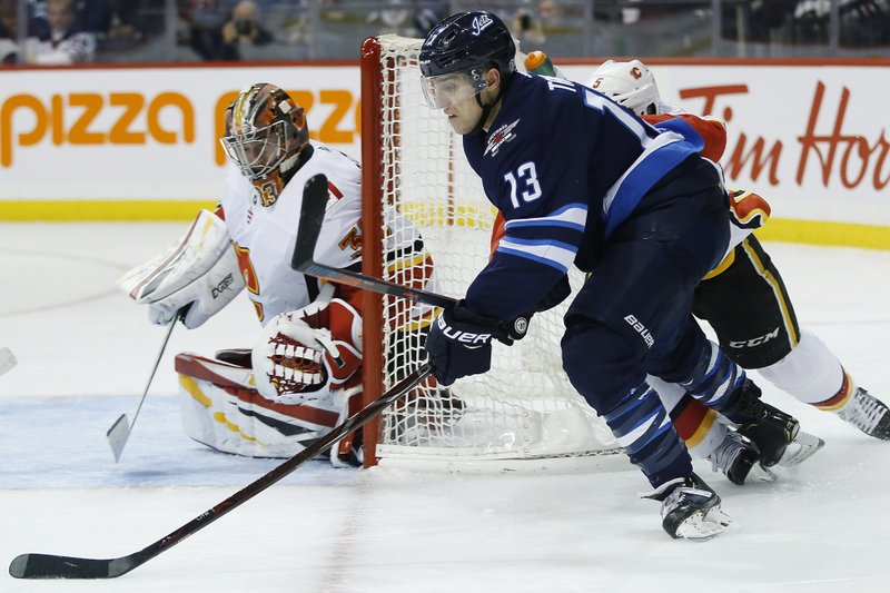Winnipeg Jets' Brandon Tanev (13) attempts a wraparound against Calgary Flames goaltender David Rittich (33) during second-period NHL hockey game action in Winnipeg, Manitoba, Thursday, Dec. (John Woods/The Canadian Press via AP)