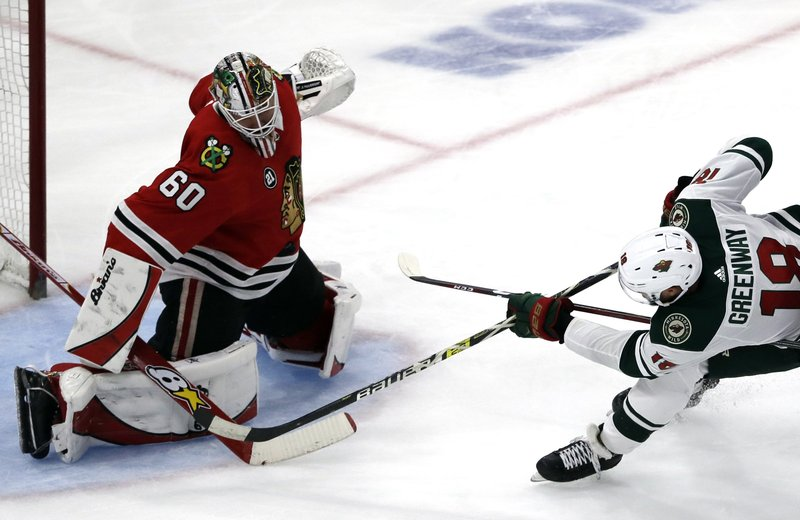 Chicago Blackhawks goalie Collin Delia, left, blocks a shot by Minnesota Wild left wing Jordan Greenway during the second period of an NHL hockey game Thursday, Dec. (AP Photo/Nam Y. Huh)
