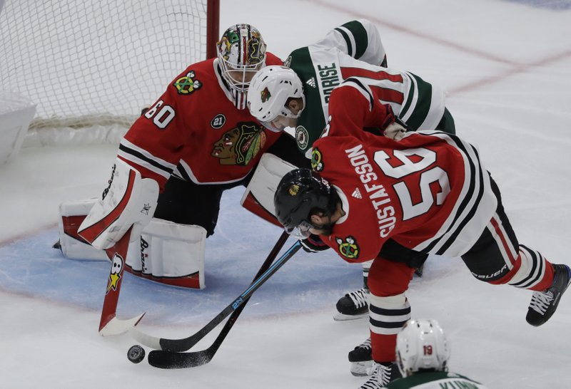 Minnesota Wild left wing Zach Parise (11) battles for the puck against Chicago Blackhawks goalie Collin Delia and defenseman Erik Gustafsson (56) during the second period of an NHL hockey game Thursday, Dec. (AP Photo/Nam Y. Huh)