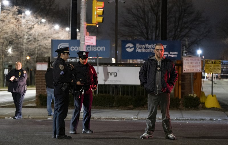 Law enforcement personnel stand in front of a Con Edison facility in the Queens borough of New York, Thursday, Dec. (AP Photo/Craig Ruttle)