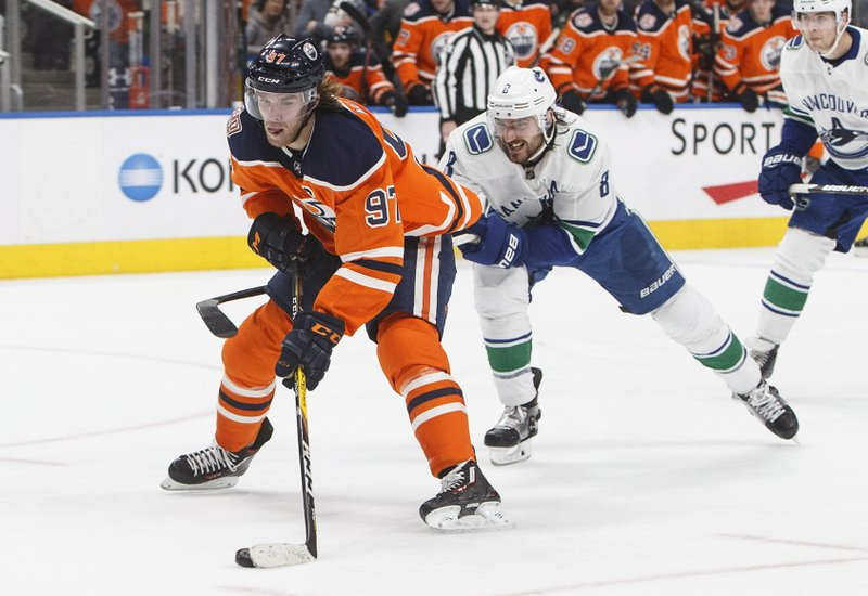 Vancouver Canucks' Chris Tanev (8) chases Edmonton Oilers' Connor McDavid (97) during the second period of an NHL hockey game Thursday, Dec. (Jason Franson/The Canadian Press via AP)