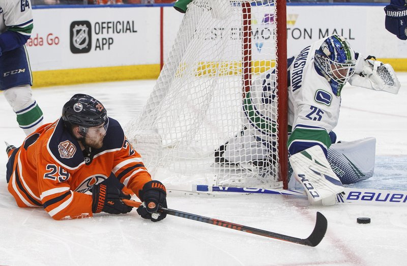 Vancouver Canucks goalie Jacob Markstrom (25) makes a save on Edmonton Oilers' Leon Draisaitl (29) during the second period of an NHL hockey game Thursday, Dec. (Jason Franson/The Canadian Press via AP)