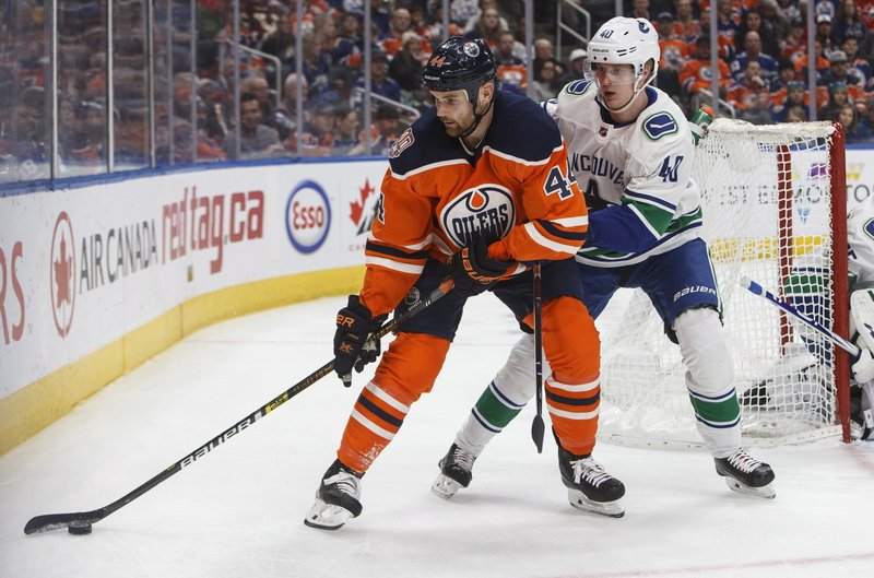 Vancouver Canucks' Elias Pettersson (40) chases Edmonton Oilers' Zack Kassian (44) during the second period of an NHL hockey game Thursday, Dec. (Jason Franson/The Canadian Press via AP)