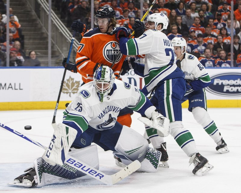 Vancouver Canucks goalie Jacob Markstrom (25) turns the puck away as Edmonton Oilers' Connor McDavid (97) and Canucks' Ben Hutton (27) work in front of the net during the second period of an NHL hockey game Thursday, Dec. (Jason Franson/The Canadian Press via AP)
