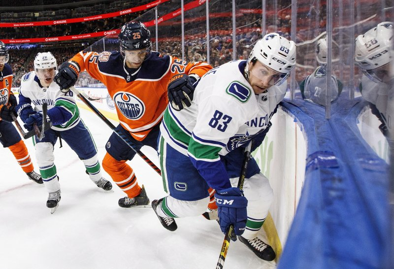 Vancouver Canucks' Jay Beagle (83) and Edmonton Oilers' Darnell Nurse (25) battle for the puck during the first period of an NHL hockey game Thursday, Dec. (Jason Franson/The Canadian Press via AP)