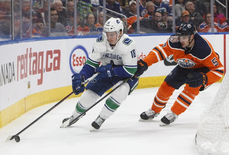 Vancouver Canucks' Jake Virtanen (18) is chased by Edmonton Oilers' Kevin Gravel (5) during the first period of an NHL hockey game Thursday, Dec. (Jason Franson/The Canadian Press via AP)