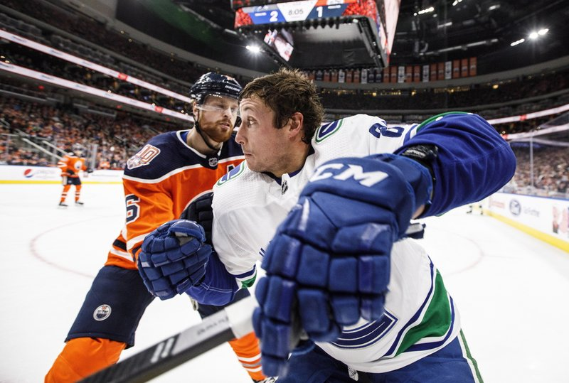 Vancouver Canucks' Jay Beagle (83) and Edmonton Oilers' Adam Larsson (6) compete for the puck during the first period of an NHL hockey game Thursday, Dec. (Jason Franson/The Canadian Press via AP)