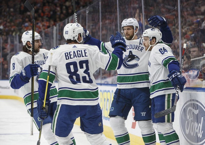 Vancouver Canucks' Chris Tanev (8), Jay Beagle (83), Alexander Edler and Tyler Motte (64) celebrate a goal against the Edmonton Oilers during the first period of an NHL hockey game Thursday, Dec. (Jason Franson/The Canadian Press via AP)