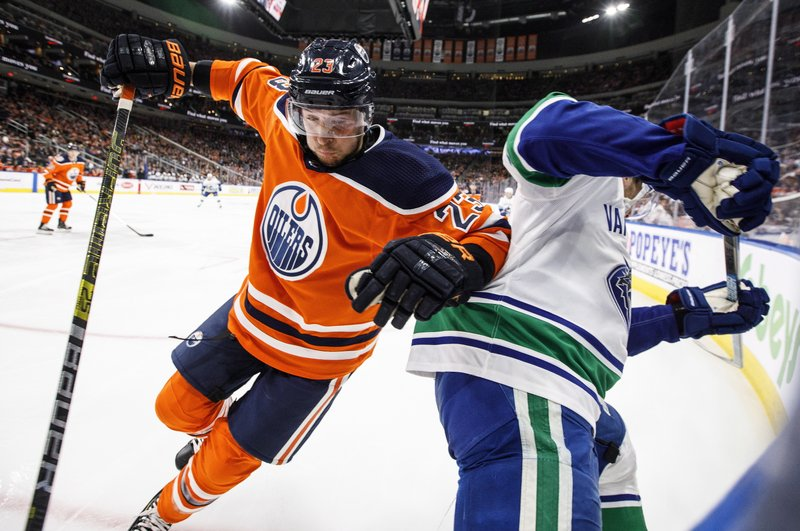 Vancouver Canucks' Bo Horvat (53) is checked by Edmonton Oilers' Ryan Spooner, left, during the first period of an NHL hockey game Thursday, Dec. (Jason Franson/The Canadian Press via AP)