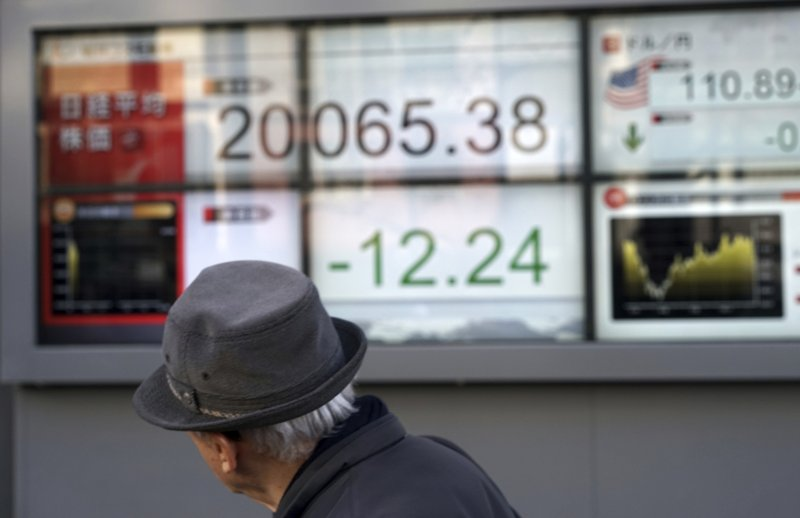 A man walks past an electronic stock board showing Japan's Nikkei 225 index at a securities firm in Tokyo Friday, Dec. (AP Photo/Eugene Hoshiko)