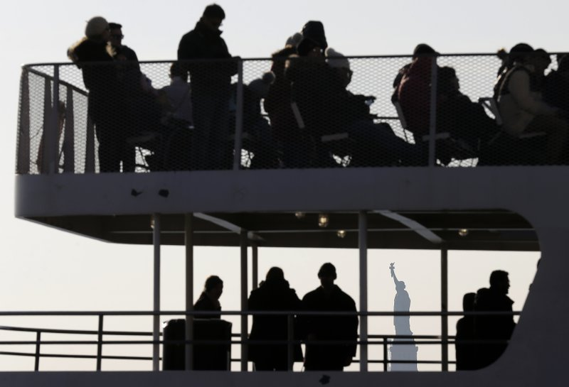 Tourists board a boat headed for the Statue of Liberty in New York, Thursday, Dec. 27, 2018. The Statue of Liberty and Ellis Island will remain open despite the ongoing partial government shutdown, even as some national parks and monuments close down, according to New York Gov. (AP Photo/Seth Wenig)