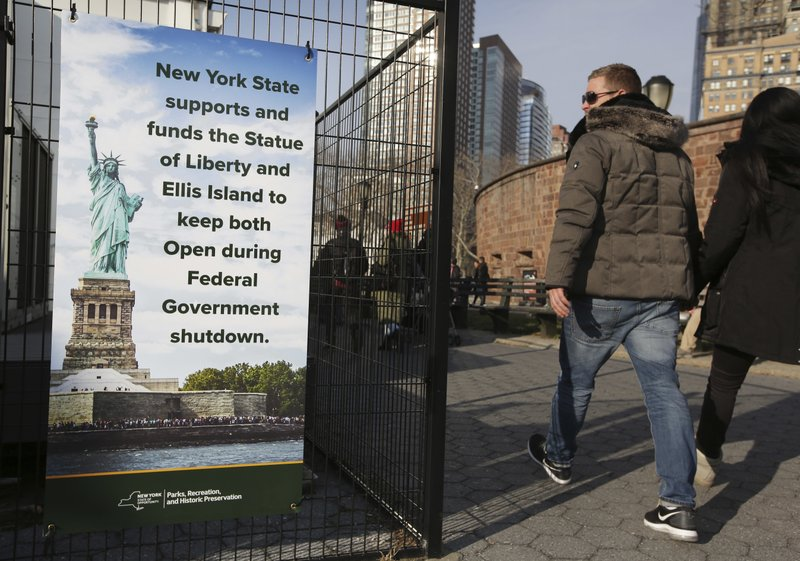 Tourists walk past a sign near the embarkation point for the Statue of Liberty in New York, Thursday, Dec. (AP Photo/Seth Wenig)