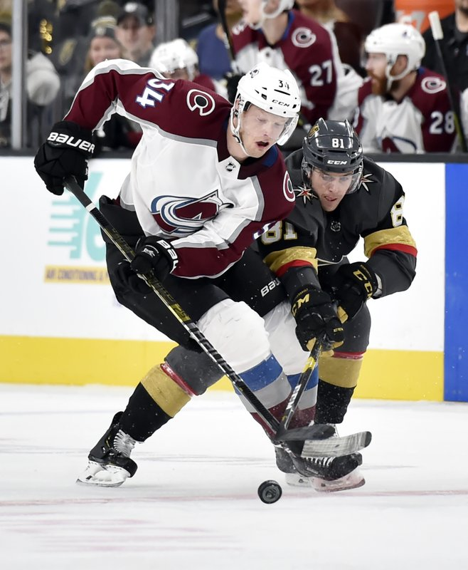 Colorado Avalanche center Carl Soderberg (34) and Vegas Golden Knights center Jonathan Marchessault vie for the puck during the third period of an NHL hockey game Thursday, Dec. (AP Photo/David Becker)