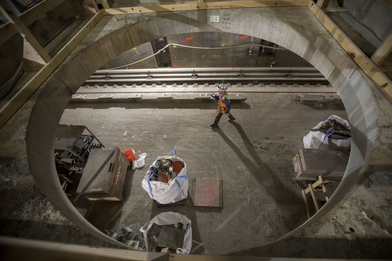 In this Nov. 29, 2018 photo, a construction worker walks on a train platform of the East Side Access project beneath Grand Central Terminal in New York. (AP Photo/Mary Altaffer)