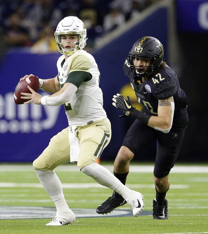 Baylor quarterback Charlie Brewer (12) looks to pass the ball as Vanderbilt linebacker Kenny Hebert (42) closes in during the first half of the Texas Bowl NCAA college football game Thursday, Dec. (AP Photo/Michael Wyke)