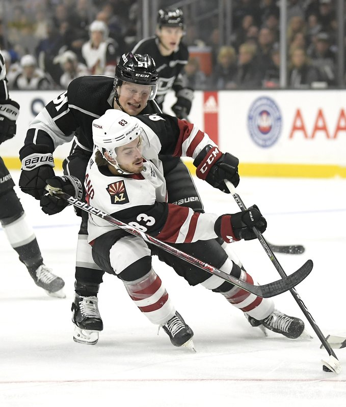 Los Angeles Kings left wing Austin Wagner, top, reaches for the puck in front of Arizona Coyotes right wing Conor Garland during the first period of an NHL hockey game Thursday, Dec. (AP Photo/Mark J. Terrill)