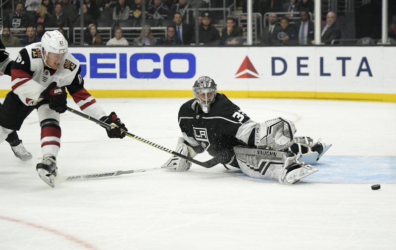 Los Angeles Kings goaltender Jonathan Quick, right, deflects a shot by Arizona Coyotes left wing Lawson Crouse during the first period of an NHL hockey game Thursday, Dec. (AP Photo/Mark J. Terrill)