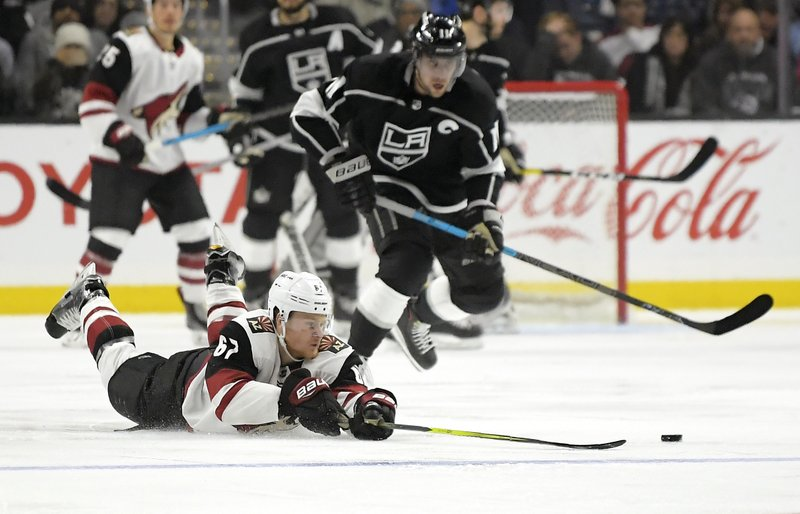 Arizona Coyotes left wing Lawson Crouse, left, dives for the puck as Los Angeles Kings center Anze Kopitar, of Slovenia, skates behind him during the second period of an NHL hockey game Thursday, Dec. (AP Photo/Mark J. Terrill)