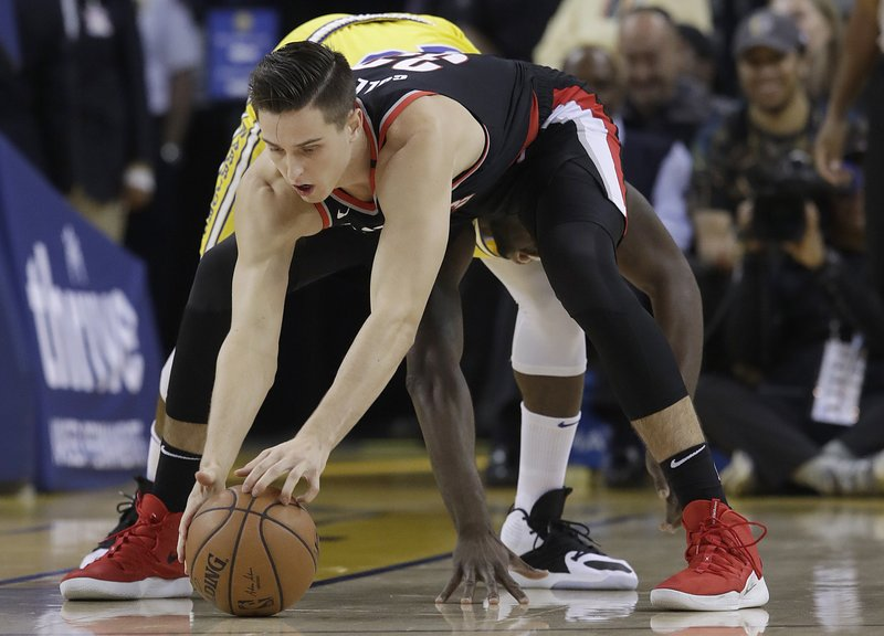 Portland Trail Blazers forward Zach Collins, foreground, reaches for the ball in front of Golden State Warriors forward Draymond Green during the first half of an NBA basketball game in Oakland, Calif. (AP Photo/Jeff Chiu)