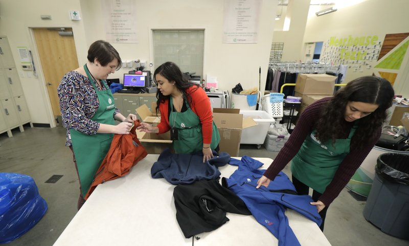 In this Friday, Dec. 21, 2018, photo, from left, Rebecca Schaechter, Nicole Herron and Rachel Herron fold and sort donated clothes at Treehouse, a nonprofit organization in Seattle that serves the needs of children in the foster-care system. (AP Photo/Ted S. Warren)
