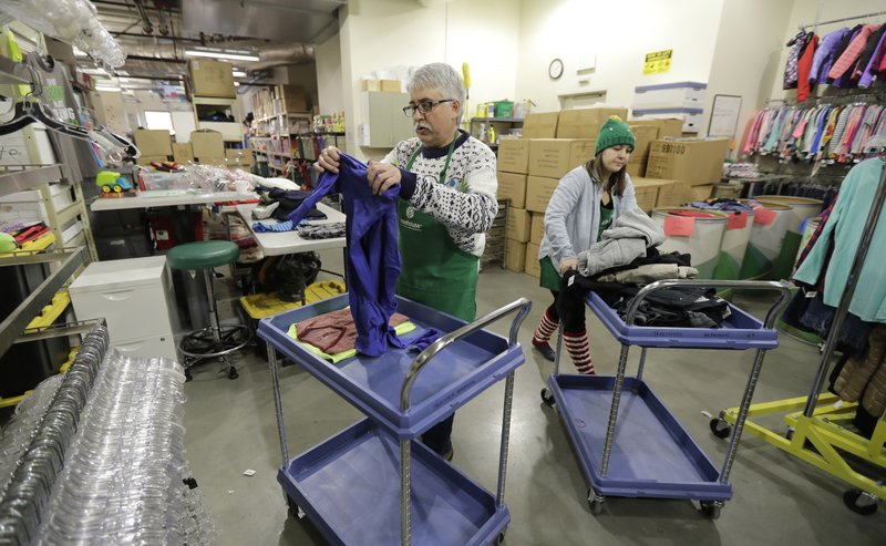 In this Friday, Dec. 21, 2018, photo, Chris Meyer, left, and Maddi Heim, fold and sort donated clothes at Treehouse, a nonprofit organization in Seattle that serves the needs of children in the foster-care system. (AP Photo/Ted S. Warren)