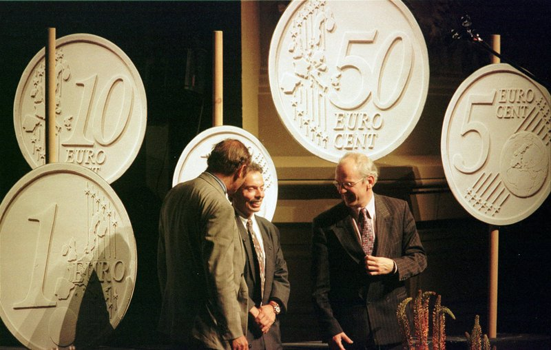 FILE - In this Monday, June 16, 1997 file photo, Belgian designer Luc Luycx, centre, is surrounded by the new Euro coins he designed during a presentation in Amsterdam. (AP Photo/Jerome Delay, File)