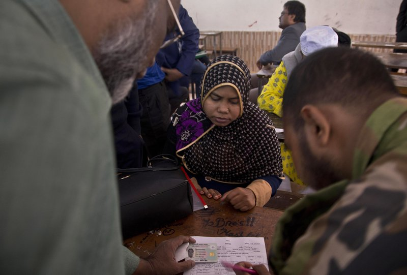 Bangladeshi election officials help a woman to find name of her family member in the voters list at a polling station ahead of the general elections in Dhaka, Bangladesh, Thursday, Dec. (AP Photo/Anupam Nath)