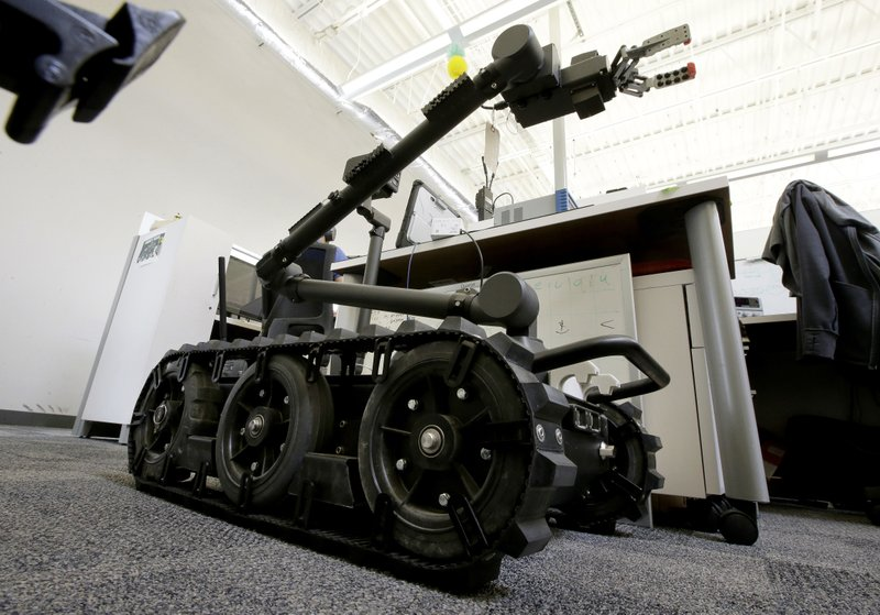 In this Aug. 28, 2018 photo a Centaur robot rests on a carpeted floor between desks at Endeavor Robotics in Chelmsford, Mass. (AP Photo/Steven Senne)