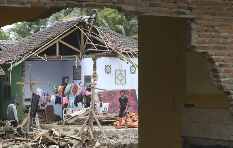 A man removes debris from his damaged home in the tsunami-hit village of Carita, Indonesia, Friday, Dec. (AP Photo/Achmad Ibrahim)