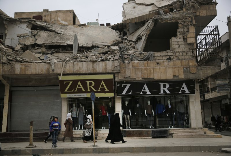 FILE - In this March 28, 2018 file photo, women walk in front of clothes shops, on a commercial street, in Manbij, north Syria. (AP Photo/Hussein Malla, File)