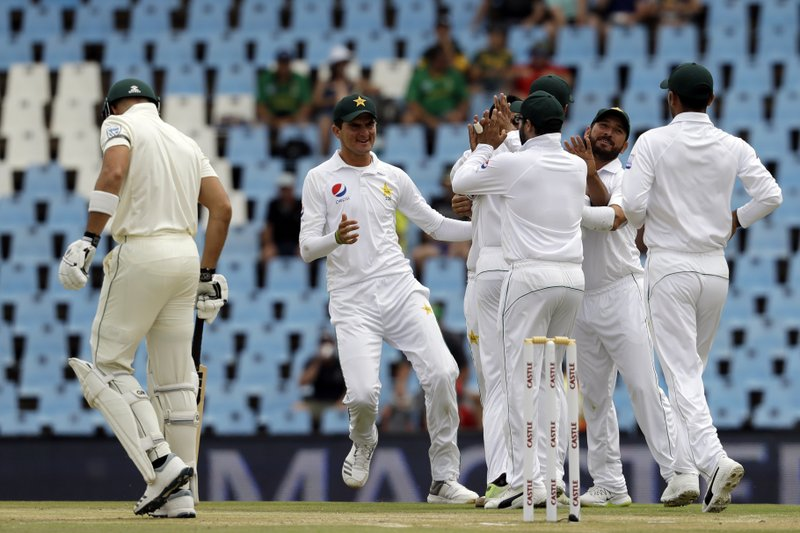 Pakistan's players celebrate the dismissal of South Africa's batsman Aiden Markram, left, for a duck on day three of the first cricket test match between South Africa and Pakistan at Centurion Park in Pretoria, South Africa, Friday, Dec. (AP Photo/Themba Hadebe)