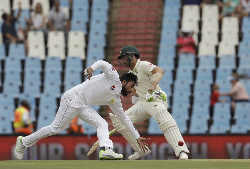 Pakistan's bowler Mohammad Amir, left, field off own bowling as South Africa's batsman Dean Elgar makes a turn on day three of the first cricket test match between South Africa and Pakistan at Centurion Park in Pretoria, South Africa, Friday, Dec. (AP Photo/Themba Hadebe)
