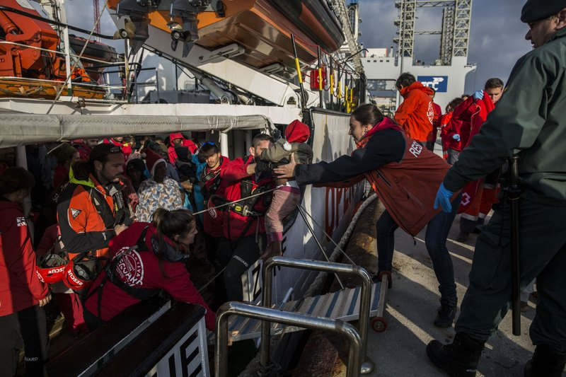 A migrant child is hekped from the Spanish NGO Proactiva Open Arms rescue vessel, after being rescued Dec. (AP Photo/Olmo Calvo)