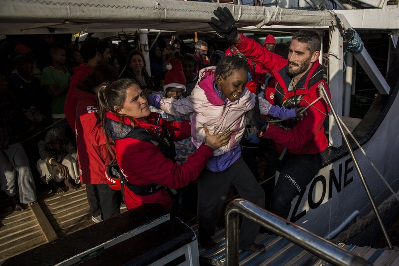 A migrant child is helped from the Spanish NGO Proactiva Open Arms rescue vessel, after being rescued Dec. (AP Photo/Olmo Calvo)