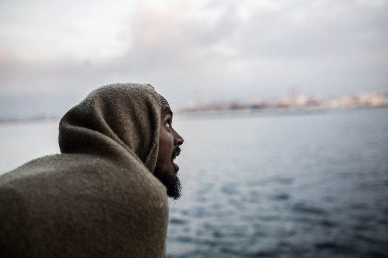A migrant looks out as they approach port, from the deck of the Spanish NGO Proactiva Open Arms rescue vessel, after being rescued in the Central Mediterranean Sea on Dec. (AP Photo/Olmo Calvo)