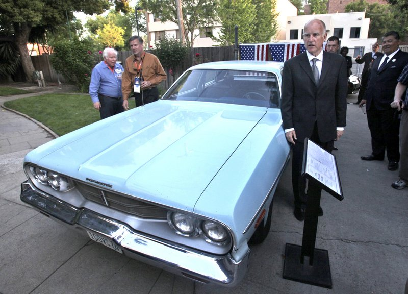 FILE - In this Saturday, April 25, 2009, file photo, Attorney General Jerry Brown, right, poses by one of the two Plymouth Satellites that he used while he was California's governor from 1975-1983, during a reception held at the Old Governor's Mansion in Sacramento, Calif. (AP Photo/Rich Pedroncelli, File)
