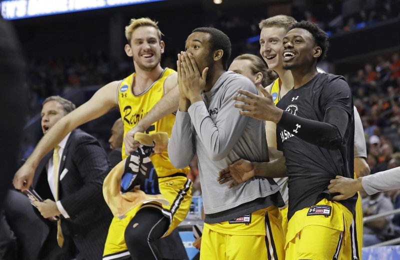 FILE - In this March 16, 2018, file photo, UMBC players celebrate a teammate's basket during the second half against Virginia i a first-round game in the NCAA men's college basketball tournament in Charlotte, N. (AP Photo/Gerry Broome, File)