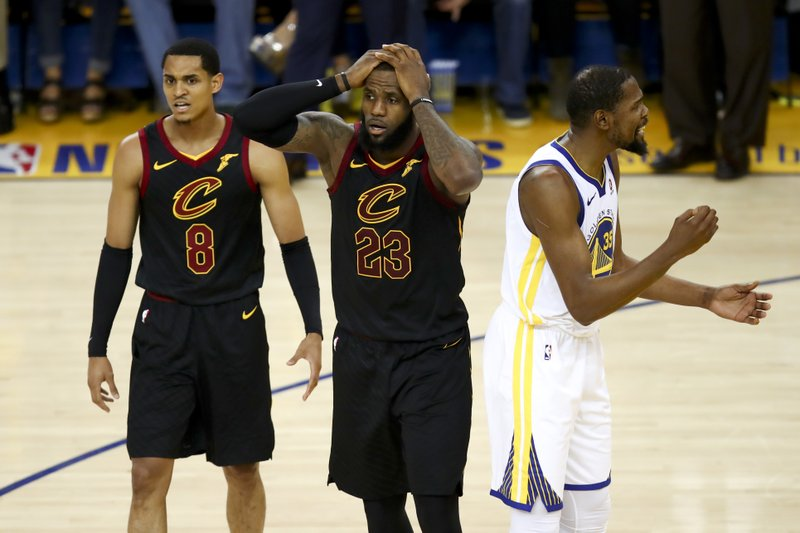 FILE - In this May 31, 2018, file photo, Cleveland Cavaliers forward LeBron James (23) reacts between guard Jordan Clarkson (8) and Golden State Warriors forward Kevin Durant during the second half of Game 1 of basketball's NBA Finals in Oakland, Calif. (AP Photo/Ben Margot, File)