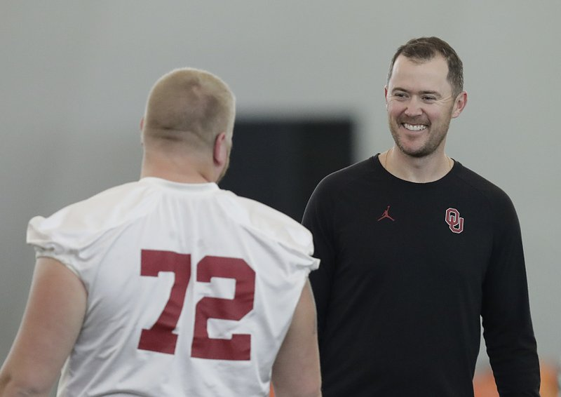 Oklahoma head coach Lincoln Riley, right, talks with Oklahoma offensive lineman Ben Powers during an NCAA college football practice Thursday, Dec. (AP Photo/Brynn Anderson)