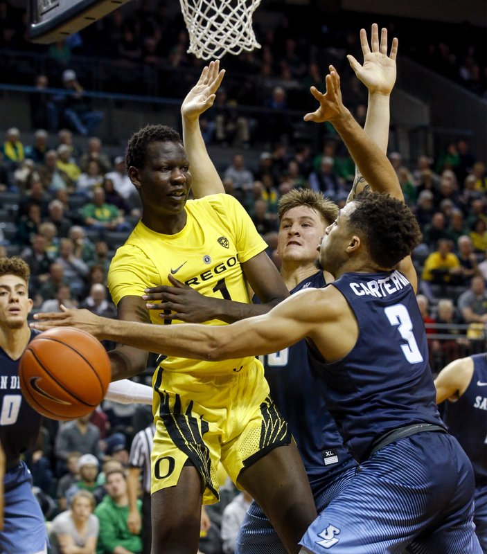 FILE - In this Dec. 12, 2018, file photo, Oregon center Bol Bol passes to teammate Payton Pritchard as he is guarded by San Diego guard Olin Carter III (3) and forward Alex Floresca late in the second half of an NCAA college basketball game in Eugene, Ore. (Andy Nelson/The Register-Guard via AP, File)