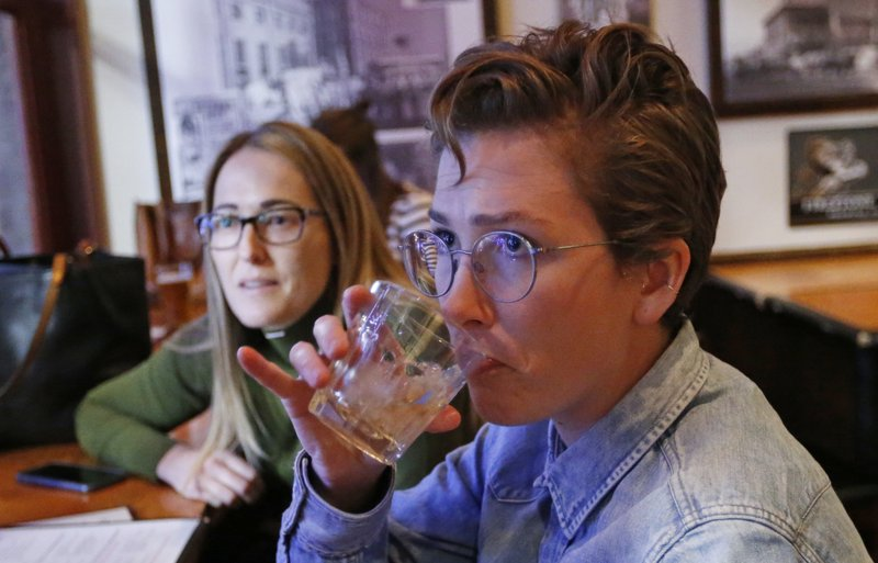 In this Dec. 20, 2018, photo, Maude Romney, 29, right, drinks at the Beer Hive Pub, in Salt Lake City. (AP Photo/Rick Bowmer)