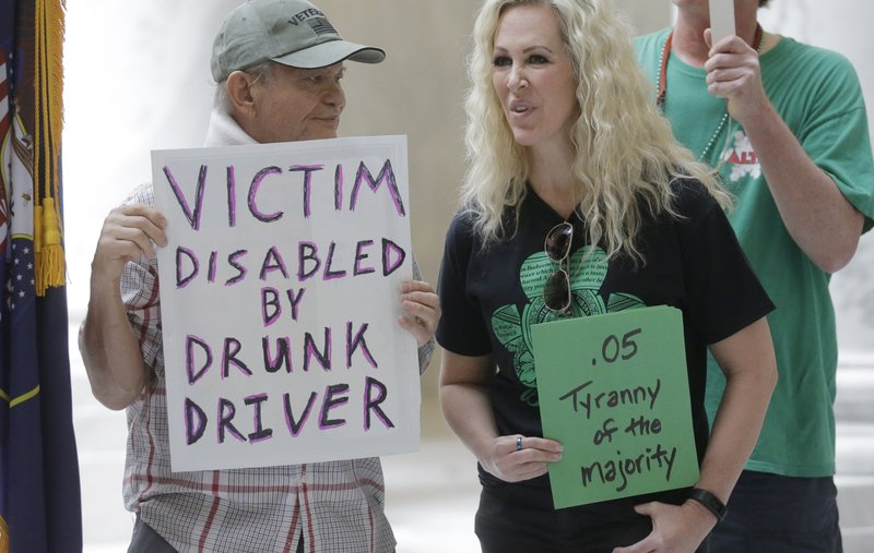 FILE - In this March 17, 2017, file photo, Ed Staley, left, and Tali Bruce, right, attend a rally concerning the DUI threshold at the Utah state Capitol in Salt Lake City. (AP Photo/Rick Bowmer, File)