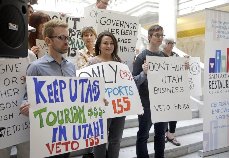 FILE - In this March 17, 2017, file photo, protesters holds signs during rally concerning the DUI threshold at the Utah state Capitol in Salt Lake City. (AP Photo/Rick Bowmer, File)