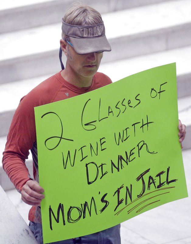 FILE - In this March 17, 2017, file photo, a protester holds a sign during a rally concerning the DUI threshold at the Utah State Capitol in Salt Lake City. (AP Photo/Rick Bowmer, File)