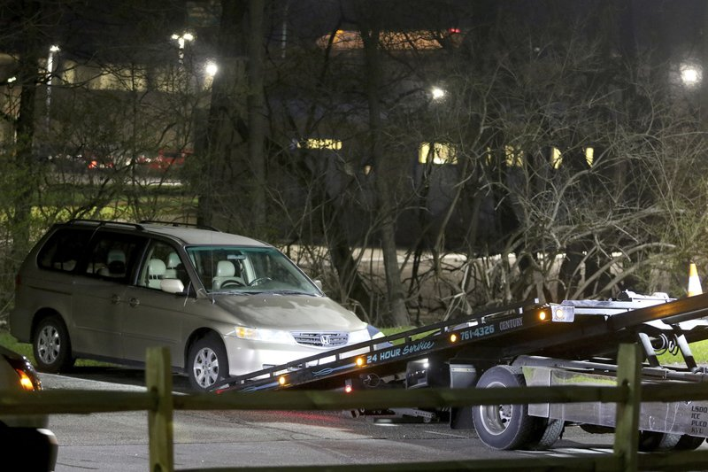 FILE - In this April 10, 2018 file photo, a minivan is removed from the parking lot near the Seven Hills School campus in Cincinnati. (Cara Owsley/The Cincinnati Enquirer via AP, File)