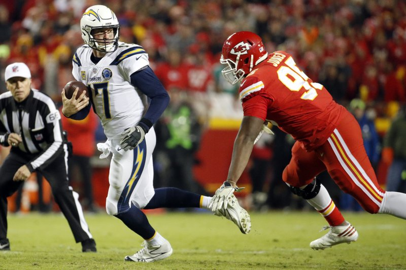 File-This Dec. 13, 2018, file photo shows Los Angeles Chargers quarterback Philip Rivers (17) running away from Kansas City Chiefs defensive end Chris Jones (95) before being sacked, during the first half of an NFL football game in Kansas City, Mo. (AP Photo/Charlie Riedel, File)